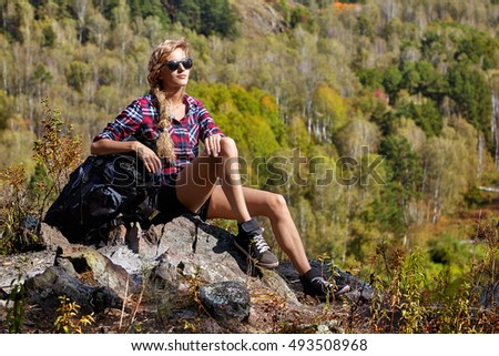 Young blonde woman tourist  with backpack sitting on a cliff on background of siberian autumn landscape. Russia, Siberia, Salair