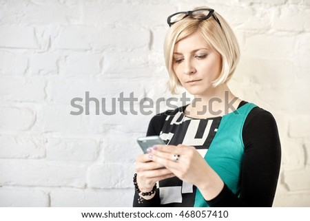 Young blonde woman using mobilephone.