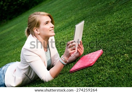 Young blonde woman using tablet outdoor laying on golf grass, smiling. - stock photo