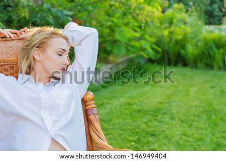 Young blonde woman wearing in man's shirt relax at outdoor sitting on a rocking chair - stock photo