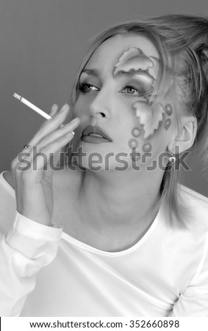 Young blonde woman with a cigarette. Scanned from black & white film.  - stock photo
