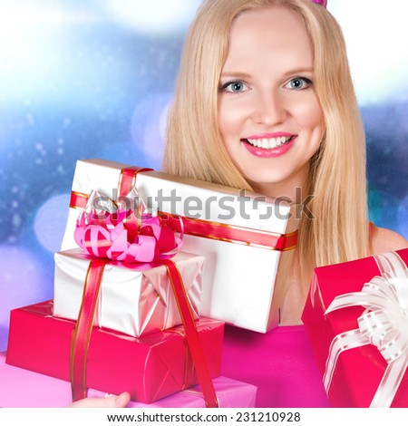 Young blonde woman with gift boxes in hands - stock photo