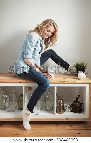 Young blonde woman with long hair sitting on wooden bench in the kitchen and smiling while holding cup of coffee to go