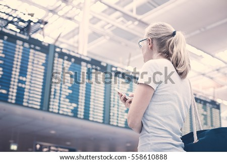 Young blonde woman with phone in her hand and shoulder bag checking flight timetable in international airport - travel concept