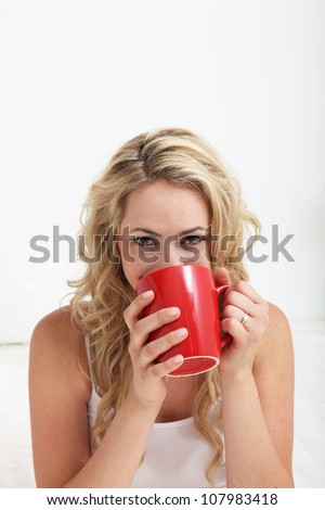 Young blonde woman with smiling eyes drinking a large mug of coffee against a white interior background - stock photo