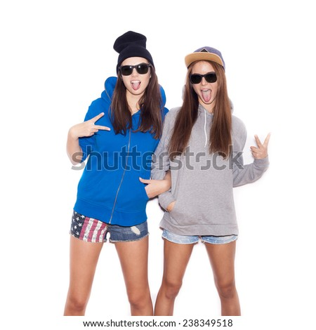 Young blonde women in sunglasses showing victory by finger. Two Fashion hipster girls.  White background, not isolated - stock photo