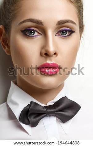 young blondie woman in white shirt and black bow-tie over white - stock photo