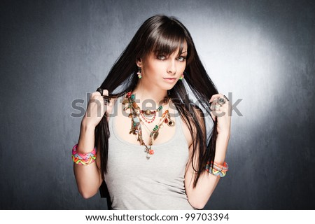 young blue eyes fashion girl portrait with lot of necklaces, rings and bracelets studio shot - stock photo