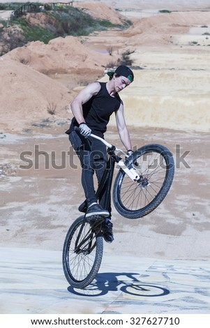 young BMX rider doing a bike stunt on a BMX session in the mountain - focus on the body - stock photo
