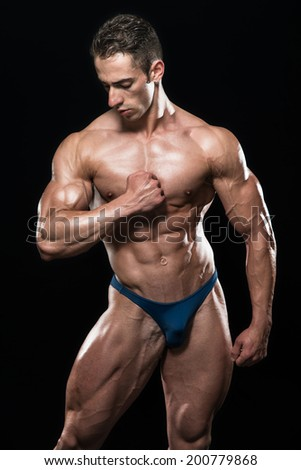 Young Bodybuilder Flexing Muscles - Isolate On Black Black ground - Copy Space