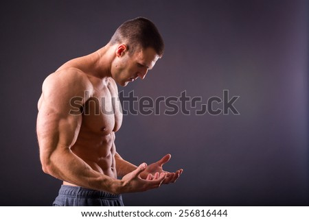 Young bodybuilder guy in good shape against a dark background. Man posing, showing his muscle definition. - stock photo