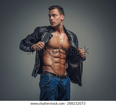 Young bodybuilder in blue jeans and black jacket. Isolated on grey background