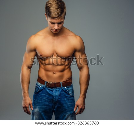 Young bodybuilder in denim jeans looking down. Isolated on grey background. - stock photo