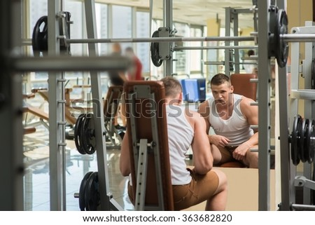 Young bodybuilder in gym. Athlete working out in gym. Sportsmen looking at the mirror in gym. - stock photo