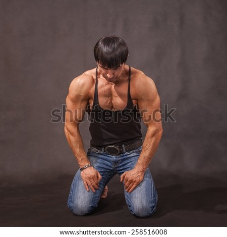 Young bodybuilder in jeans and a black T-shirt is on his knees in the studio on a gray background - stock photo