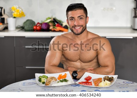 young bodybuilder in the kitchen, smiling, with two plates of healthy food: rice, chicken grill, broccoli, carrots, mushrooms, salmon, tomato, red peppers, potatoes - stock photo