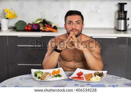 young bodybuilder in the kitchen, with two plates of healthy food: rice, chicken grill, broccoli, carrots, mushrooms, salmon, tomato, red peppers, potatoes - stock photo