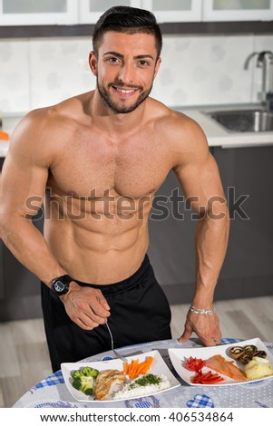 young bodybuilder in the kitchen with two plates of healthy food: rice, chicken grill, broccoli, carrots, mushrooms, salmon, tomato, red peppers, potatoes - stock photo