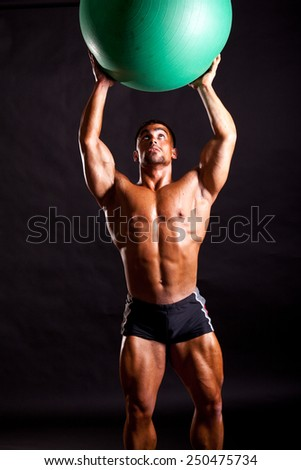 young bodybuilder posing in studio with fitball - stock photo