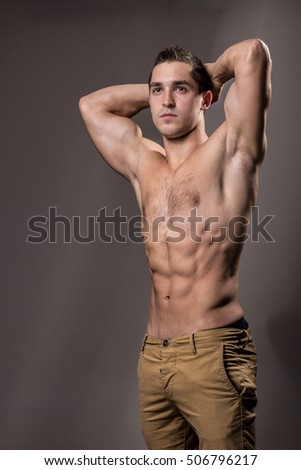 young bodybuilder posing strong muscular torso, chest, abs, arms up. pants, studio.