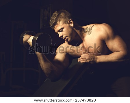 Young bodybuilder training in a gym - stock photo