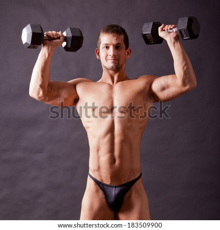 young bodybuilder traininig over balck background - stock photo