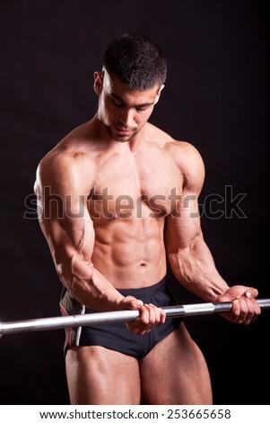 young bodybuilder traininig over black background - stock photo