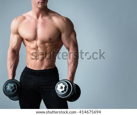 Young bodybuilder with dumbbells in studio - stock photo