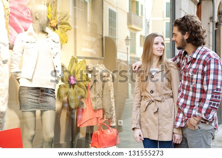 Young bohemian couple looking at clothes in a store window while on vacations in a destination city, smiling.