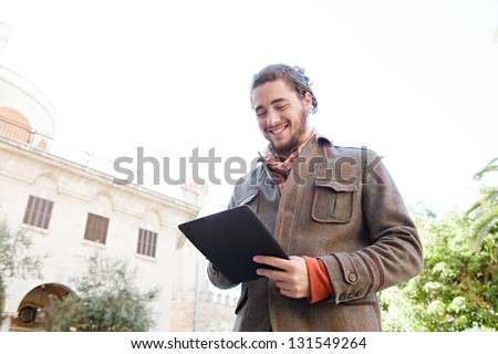 Young bohemian man using a digital tablet pad while smiling visiting an old destination city during a sunny day, on vacation. - stock photo