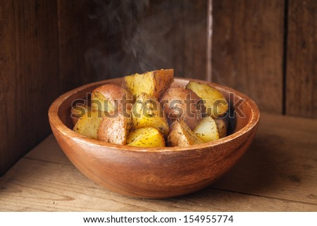 Young boiled potatoes in wooden bowl - stock photo