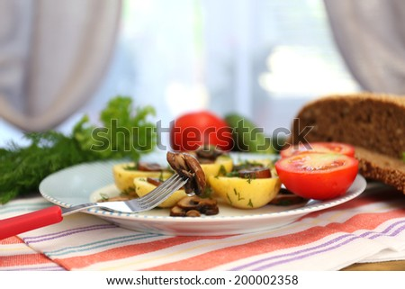 Young boiled potatoes on table on window background