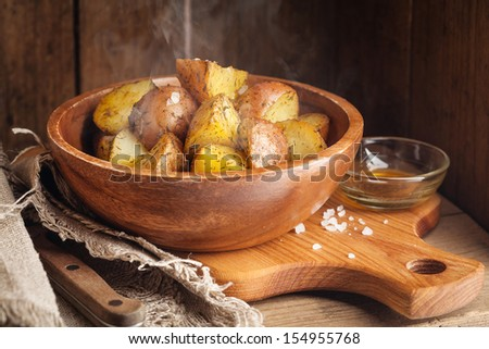 Young boiled potatoes with dill and oil in wooden bowl - stock photo