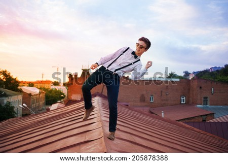 Young bold girl woman hipster jumping on the roof, dressed like a boy man in a shirt, bow-tie, suspenders and pants trousers - stock photo