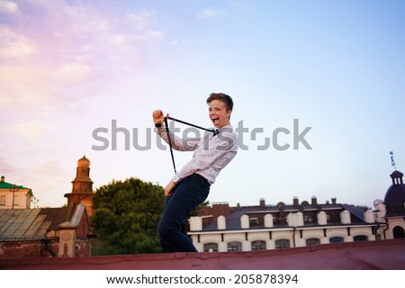 Young bold girl woman hipster on roof showing off tongue and stretching suspenders - stock photo