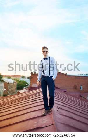 Young bold guy boy girl woman in hipster clothes on edge of roof, dressed like a boy man in shirt, bow-tie, suspenders and pants trousers on background of city - stock photo