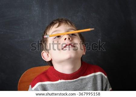 Young bored boy balancing a pencil on his nose. - stock photo