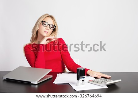 Young bored business woman sitting at work desk in office - stock photo