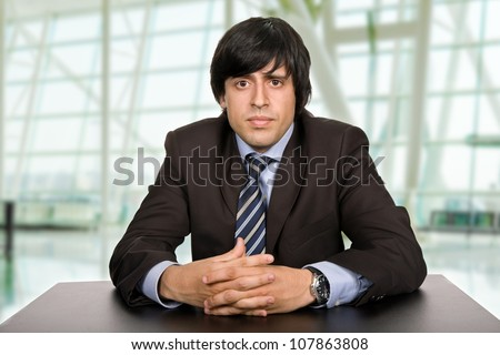 young bored businessman on a desk at the office - stock photo