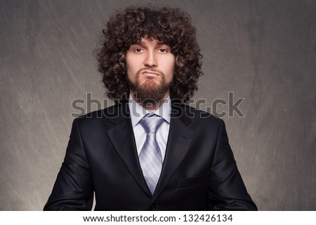 young bored businessman with afro style hair making a facial expression that explains his mood on grunge background - stock photo