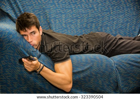 Young bored man sitting on sofa watching television changing the channel with the remote control - stock photo