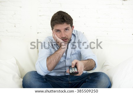 young bored man watching tv sitting at home living room sofa looking tired and not having fun with the television program or movie using remote control for changing to another channel - stock photo