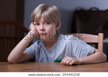 Young bored schoolboy sitting at the table - stock photo