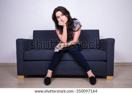 young bored woman sitting on sofa and watching tv at home - stock photo