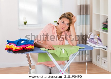 Young Bored Woman Sitting With Electric Iron And Clothes At Ironing Board - stock photo
