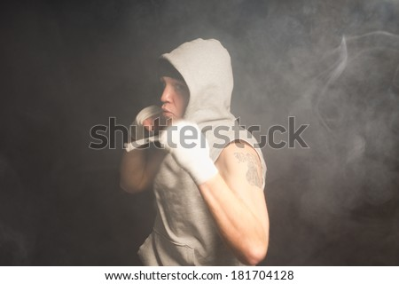 Young boxer about to throw a punch turned at an angle to the camera with his arm drawn back about to launch himself forwards in a dark smoky environment - stock photo