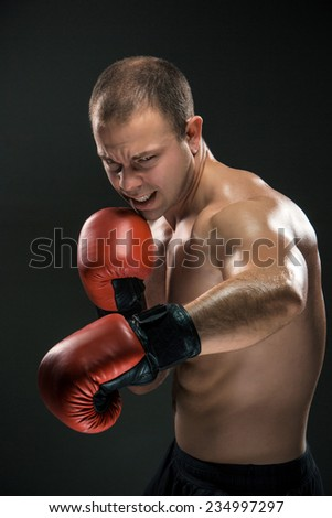 Young boxer  boxing over black background