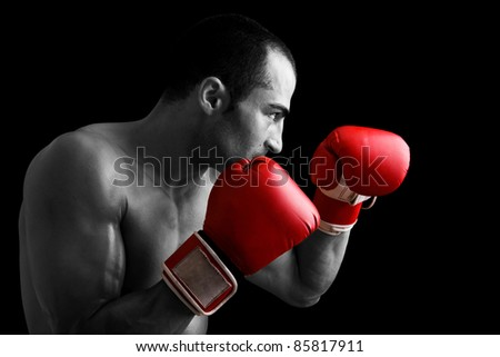 Young Boxer fighter over black background - stock photo