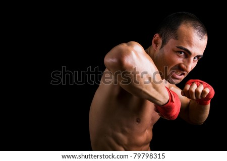 Young Boxer fighter over over black background