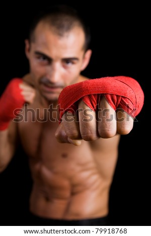 Young Boxer fighter over over black background. Focus on hand. - stock photo